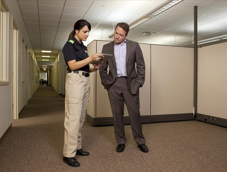 Two people standing, on the left is a SERVPRO representative, on the right is a business professional. Both discussing plans.